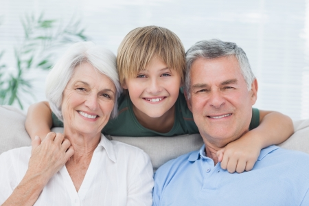 Grandson embracing his grandparents in living room Stock Photo - 20638543