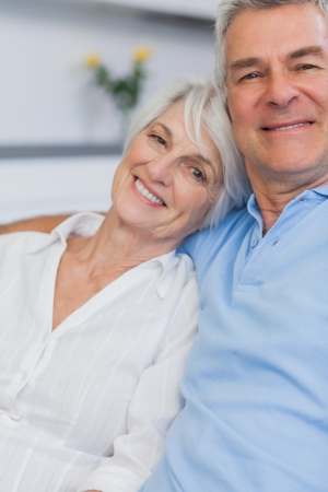 an elderly couple: Elderly couple embracing in the kitchen Stock Photo
