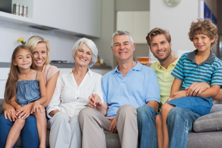 Extended family sitting on couch in living room and smiling at camera photo