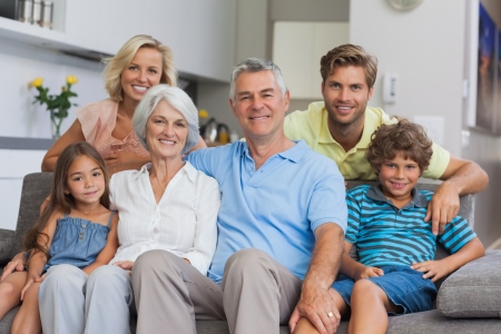 woman on couch: Multi-generation family posing in the living room and smiling at camera Stock Photo