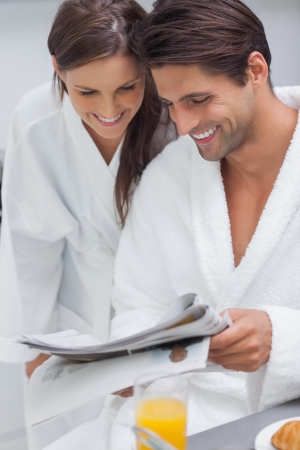 Lovely couple wearing bathrobes and reading newspaper photo