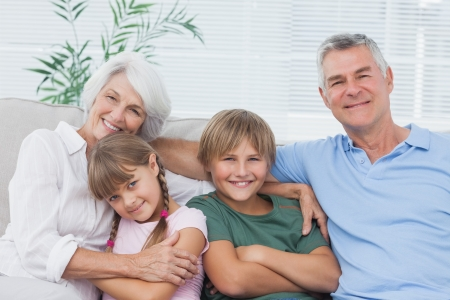 Portrait of grandparents with their grandchildren sitting on couch Stock Photo - 20639908