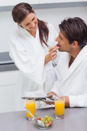 Woman wearing bathrobe feeding her husband strawberry in kitchen photo