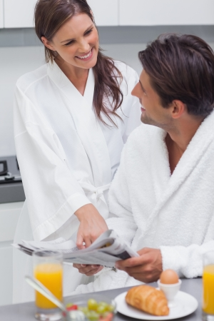 Young couple having breakfast in the kitchen photo