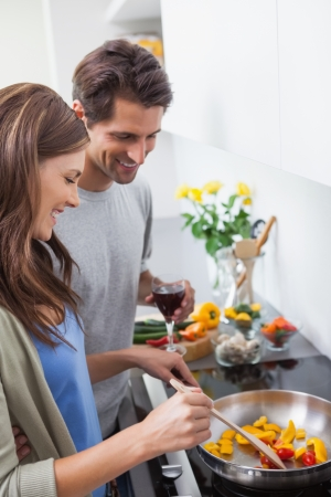 Couple cooking together vegetables in kitchen photo