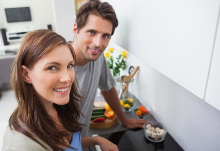 Couple cooking and smiling at camera photo