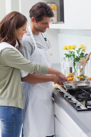 Delighted couple cooking in the kitchen photo
