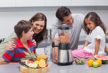Family using a blender in the kitchen photo