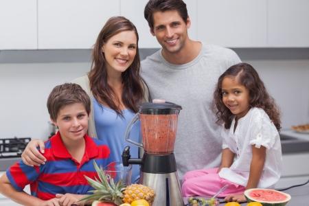 licuadora: Familia posando con una batidora en la cocina