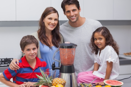 Family posing with a blender in the kitchen photo