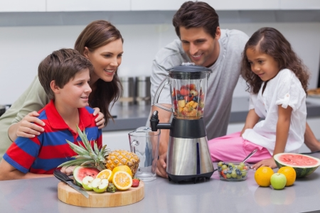 Smiling family using a blender in the kitchen photo