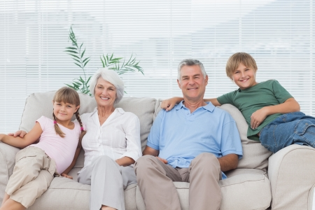 Grandparents and grandchildren sitting on couch in the living room photo