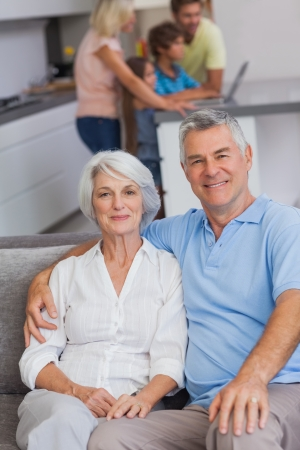 with fondness: Portrait of a couple sitting on couch with their family in the kitchen behind them