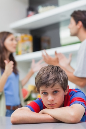Sad little boy listening to his parents arguing in the kitchen photo