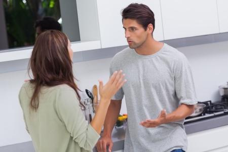 angry couple: Pareja joven discutiendo en la cocina