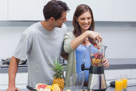 Couple putting various fruits into blender photo