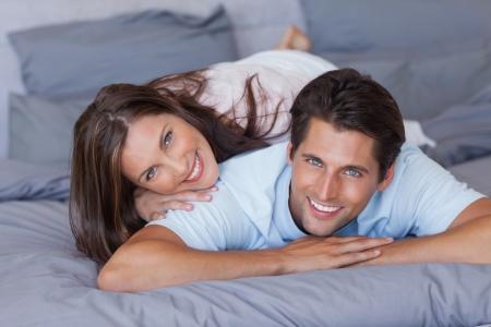 hair short: Bonita pareja sonriendo a la c�mara y acostado en la cama