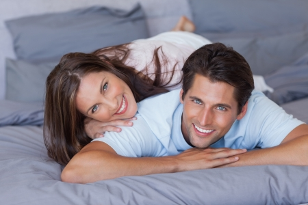 man long hair: Lovely couple smiling at camera and lying on bed Stock Photo