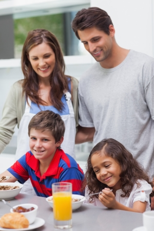Parents looking at their children having breakfast in the kitchen Stock Photo - 20639252