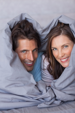 hair wrapped up: Delighted couple having fun wrapped in their duvet at home