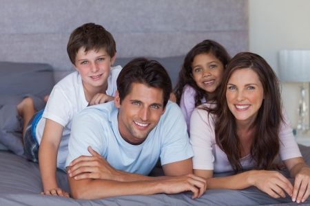 multiracial family: Happy family lying on bed and looking at camera