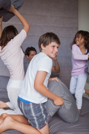 Happy family having a pillow fight on the bed at home photo