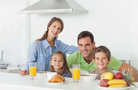 Portrait of cute family having breakfast at home in kitchen