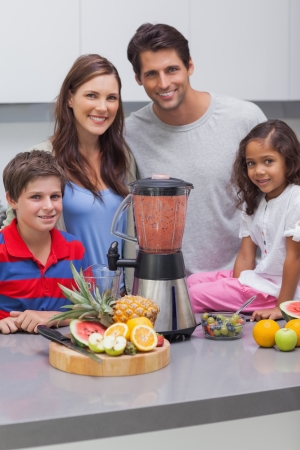 Smiling family using a blender together in the kitchen photo