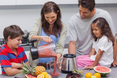Woman with family pouring fruit from a blender into a cup photo