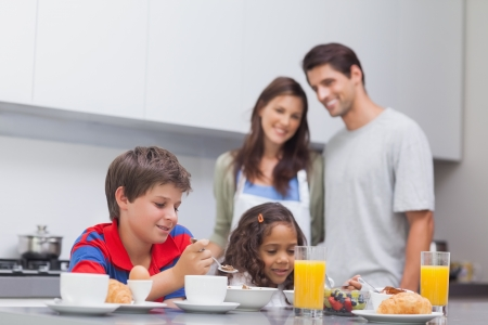 breakfast: Children having breakfast in kitchen while their parents are looking at them  Stock Photo