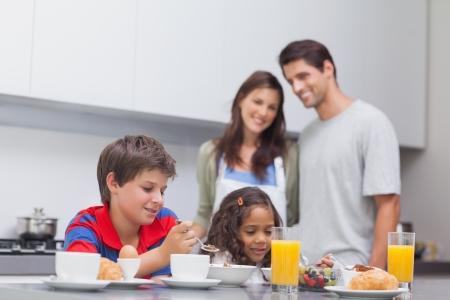 niños desayunando: Los niños que desayunan en la cocina mientras sus padres están viendo ellos