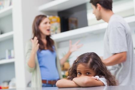 verdrietig meisje: Verdrietig meisje luistert naar haar ouders ruzie in de keuken