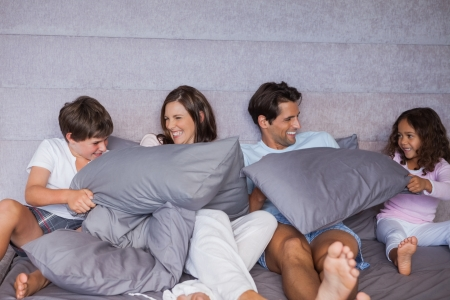 pijama: Familia que se divierte junto en la cama en su casa