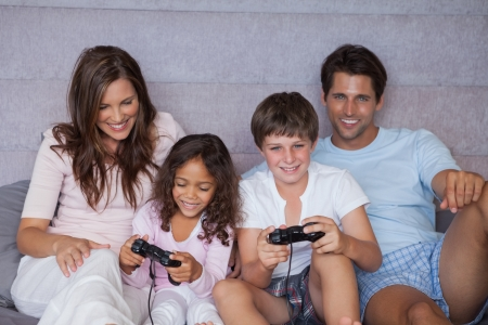 Smiling family playing video games on bed photo