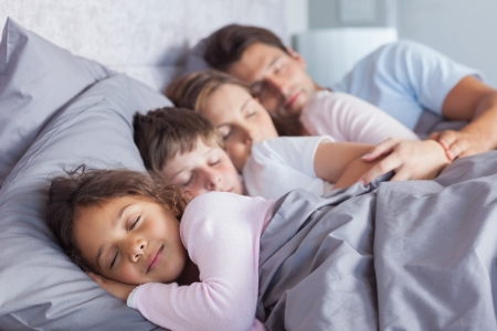 Cute family sleeping together in bed Фото со стока - 20640603