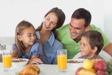 padres hablando con hijos: Los padres de desayunar con sus hijos en la cocina Foto de archivo