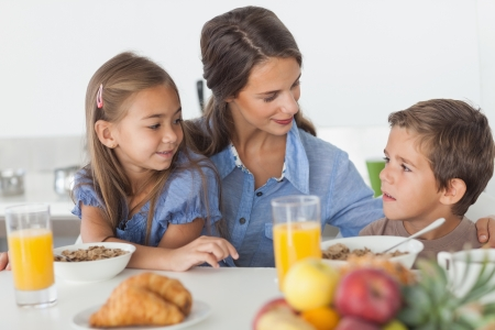 Pretty mother having breakfast with her children in the kitchen photo