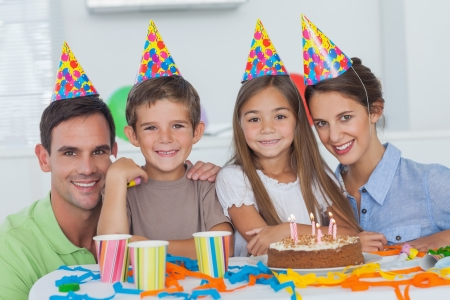 party table: Family wearing party hat and celebrating a birthday  Stock Photo