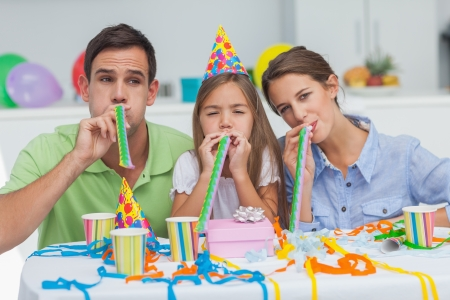 Family playing with party horns during a birthday party photo