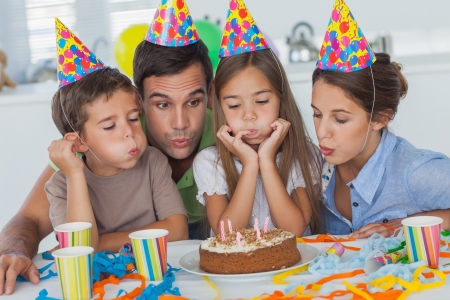 Family blowing candles together while celebrating a birthday party photo