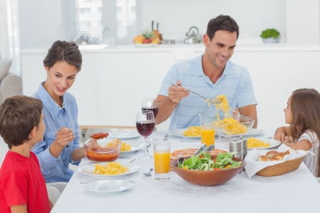 Family dining on pasta together at home in kitchen photo