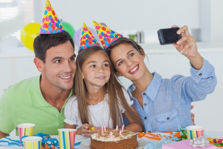 Woman taking pictures of her family during her daughter birthday party photo