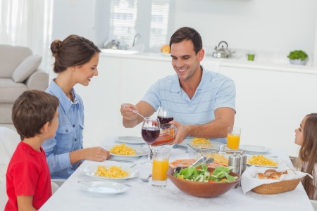 familia cenando: El hombre que sirve esposa durante la cena familiar