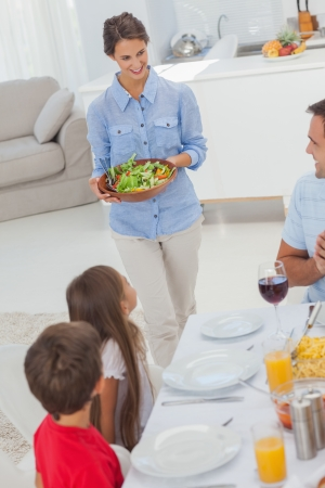 bringing: Woman bringing a salad to her family for the dinner Stock Photo