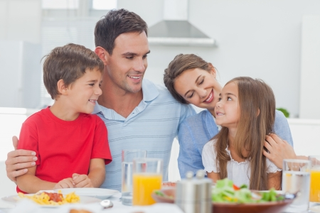 family meal: Cute family during the dinner at the table at home Stock Photo