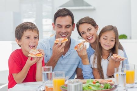 familia comiendo: Familia que come las porciones de pizza para la cena Foto de archivo
