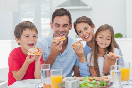 pizzas: Family eating pizza slices for the dinner
