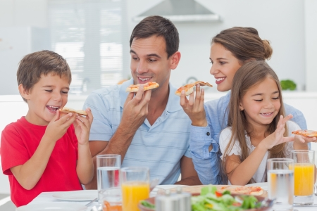 Happy family eating pizza slices for the dinner photo
