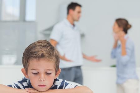 Droevige jongen terwijl de ouders ruzie in de keuken