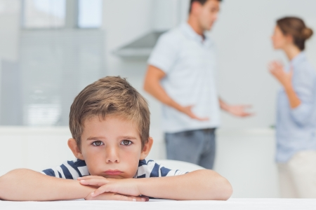 angry: Sad boy with arms folded while parents quarreling in the kitchen